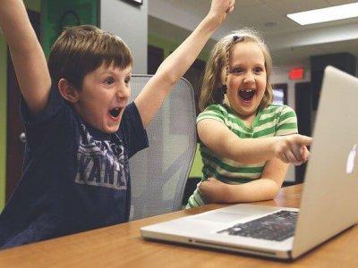 Kinder freuen sich und zeigen auf Laptop